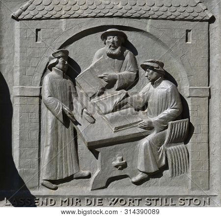 ZURICH, SWITZERLAND - JUNE 23, 2018: Work on the translation of the Bible, from left: Leo Jud, Theodor Bibiliander and Zwingli, relief on the door of Grossmunster (