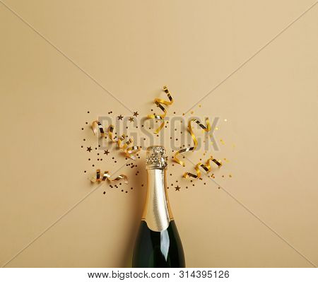 Bottle of champagne with gold glitter and bow on white background, top view. Hilarious celebration poster