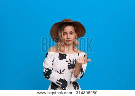 Grumpy young model with curly blond hair in a sundown hat and white dress invites with a finger standing on a blue background. poster