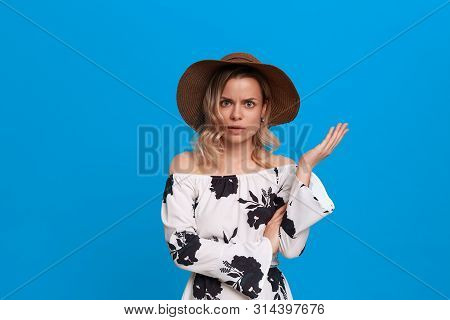 Grumpy Young Model With Curly Blond Hair In A Sundown Hat And White Dress Looks At The Camera Standi