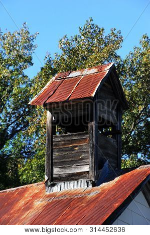Church Bell Tower Is Roofed With Tin That Has Rusted And Bent.  Tower Is Wooden And Boards Are Weath