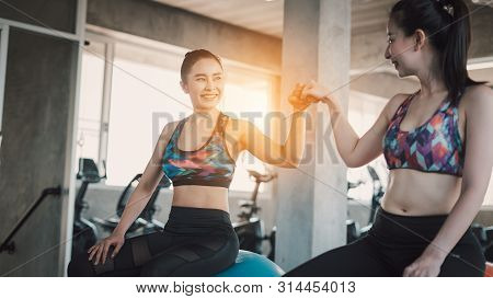 Beautiful Asian Women Working Out In Gym Together.two Attractive Fitness Girls Doing Push Ups.