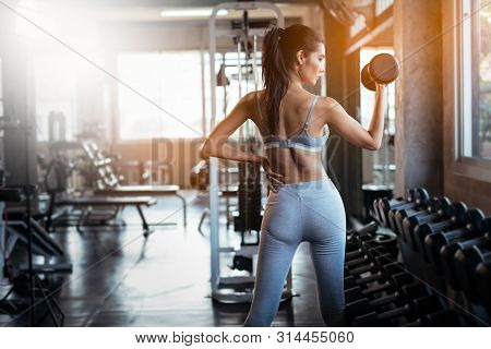 Young Asian Girl Playing Dumbbell To Exercise In Fitness.slim Girl Lifts Heavy Dumbbell While Traini