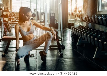 Young Woman With Earphones Listening To Music After Hard Workout In Gym. Relax Concept. Strength Tra