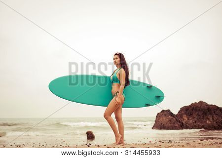 Beautiful Young Sexy Asian Surfer Girl On The Beach With Sunset. Extreme Summer Water Sport, Surfing