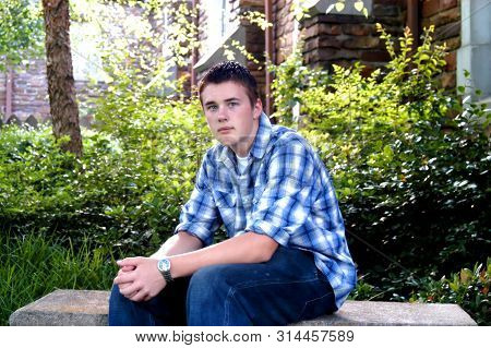 Young Teen Sits On A Garden Bench And Relaxes.  He Has A Solemn Look On His Face.  He Has On Jeans A