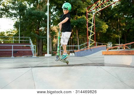 A boy on a scooter and in protective helmet do incredible stunts in skate park. Extreme jump. The concept of a healthy lifestyle and sports leisure poster