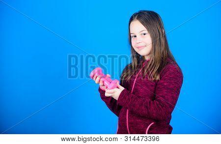 Sport for teens. Easy exercises with dumbbell. Toward stronger body. Rehabilitation concept. Girl exercising with dumbbell. Beginner dumbbell exercises. Child hold little dumbbell blue background poster