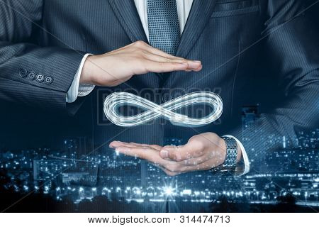 Concept Of Unlimited Internet. Businessman Shows Sign Of Infinity On The Background Of The City. The