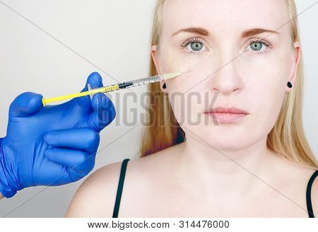 A cosmetologist carries out a procedure - an injection into the face of a young woman. Beauty injections, mesotherapy, hyaluronic acid injections, biorevitalization, cheek correction, fillers poster