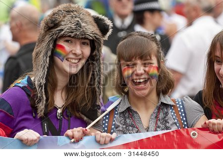 EXETER - MARCH 31: Festival goers with painted faces hold the rainbow banner at the Exeter Pride 201