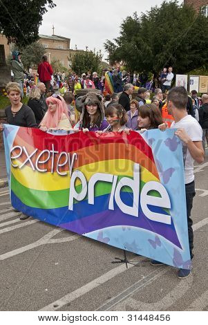 Festival goers hold up the Exeter Pride banner