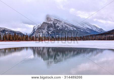 Cold Winter Morning With Low Clouds On Mount Rundle Reflecting Off Vermilion Lakes In The Canadian R