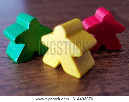 Three Meeples. Wooden Background. Colored Token. Funny Game Tokens. Green, Yelow And Red Meeple.