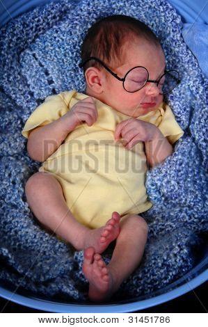 Sleeping newborn wearing glasses