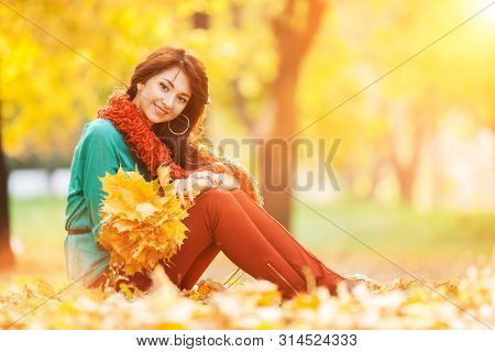 Young pretty woman relaxing in the sunny autumn park. Beauty nature scene with colorful foliage background, yellow trees and leaves at fall season. Autumn outdoor lifestyle