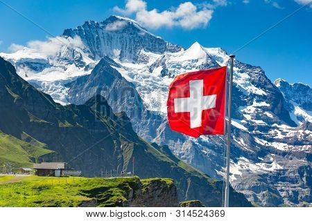 Swiss Flag Wavingon A Mannlichen Viewpoint With Peak Of Jungfrau Mountain On The Background, Bernese