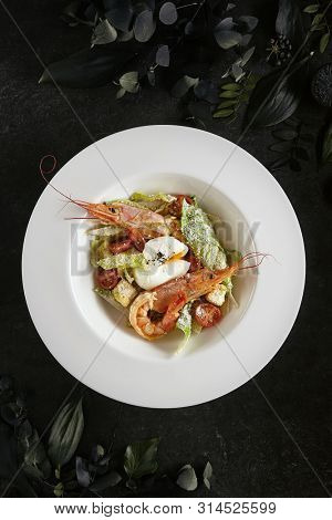 Exquisite Serving White Restaurant Plate of Caesar Salad with Shrimps, Chicken, Croutons, Tomatoes, Cucumbers Top View. Beautiful Delicacy Seafood Cesar Salat on Black Marble Background poster