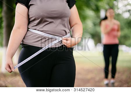 Motivation, Weight Loss, Active Lifestyle, Group Training, Personal Coach. Fat Woman Measuring Her W