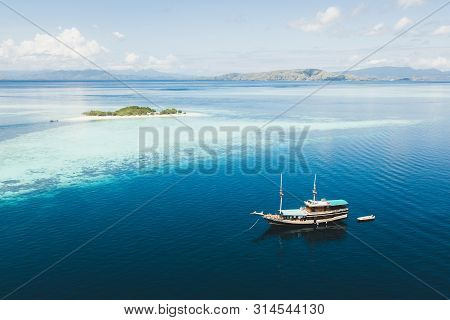 Luxury Cruise Boat Sailing Near Coral Reef Atoll Island With Amazing White Tropical Beach And Mounta