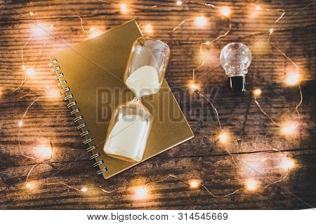 Time To Accomplish Your Goals Hourglass, Lightbulb And To Do List Notebook Surrounded By Fairy Light