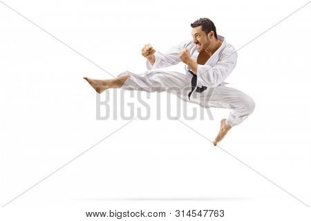 Full length shot of a man performing flying kick in martial arts isolated on white background