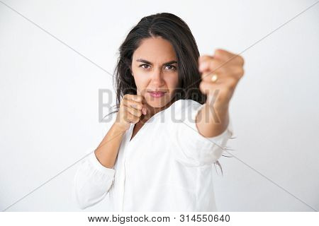 Determined Aggressive Woman Showing Boxing Or Fight Gesture. Angry Young Latin Woman In White Shirt
