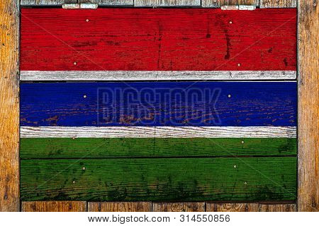 National flag of Gambia on a wooden wall background.The concept of national pride and symbol of the country.Flag painted on a wooden fence with metal nails. poster