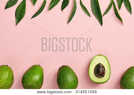 Avocado and green leaves pattern on pink background. Top View. Pop Art design, creative summer food concept. Green avocadoes, eco and healthy food minimal flat lay. Organic frame food minimal with cop