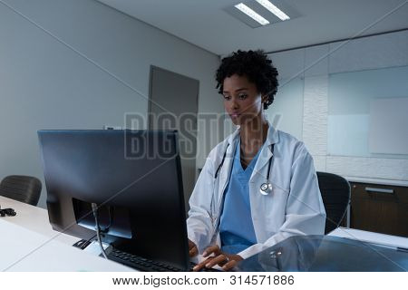 Front view of African-american female doctor working on computer at desk in hospital. Shot in real medical hospital with doctors nurses and surgeons in authentic setting