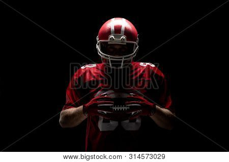 American football player standing with rugby helmet and ball against black background. Strong American Football Player concept for Championship Football Tournament