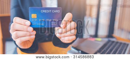 Woman Hand Holds A Blue Credit Card.and Are Using A Laptop Computer.web Banner.