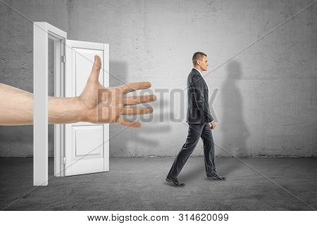 Big Male Open Hand Reaching Through White Doorway To Young Businessman Who Is Walking Away On Grey W