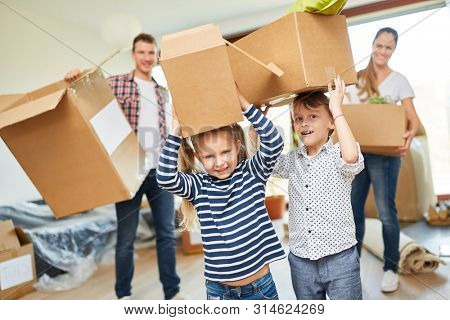 Children help parents with the move and carry moving boxes to the new house