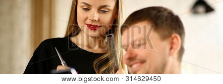 Man Client Showing Phone to Woman Hairdresser. Female Hairstylist Holding Scissors and Hairbrush in Hands. Smiling Male Customer Sitting in Beauty Salon. Beautiful Blonde Stylist with Guy in Studio poster