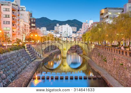 Nagasaki, Japan cityscape with Megane Spectacles Bridge at dusk.