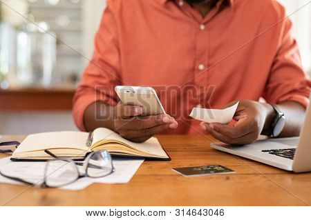 Closeup of african man hands using phone to calculate expenses. Man checking invoice balance on mobile phone app. Close up hands of black guy looking his budget and calculating credit card bills.