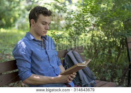 Young Man Reading A Book In Park