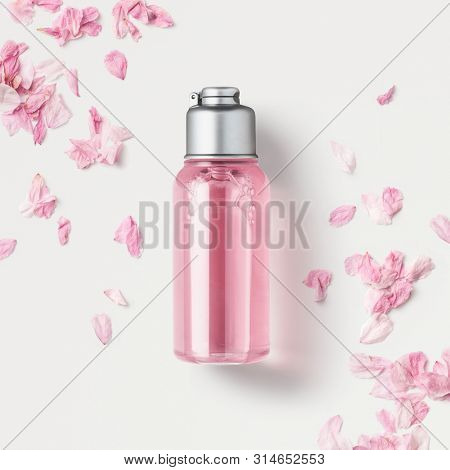 cosmetics packaging design concept or mock-up with blank transparent bottle with pink liquid soap or shower gel on a white surface surrounded by delicate cherry flower petals, top view / flat lay