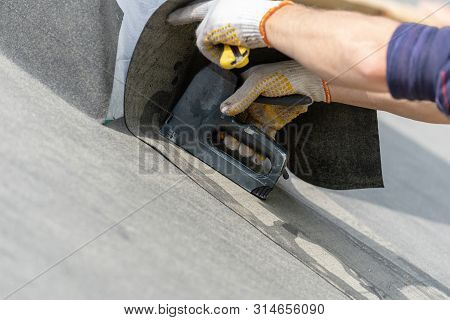 Man Using Stapler And Attact Special Waterproof Bitumen Membrane. Close Up, Cropped Photo Of Hands Q