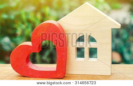 House With A Red Wooden Heart On A Green Background. House Of Lovers. Affordable Housing For Young F