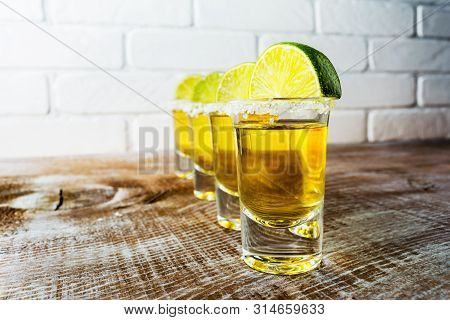 Gold Mexican Tequila Shots With Lime Slices On The Rustic Wooden Background And Painted Brick Wall.