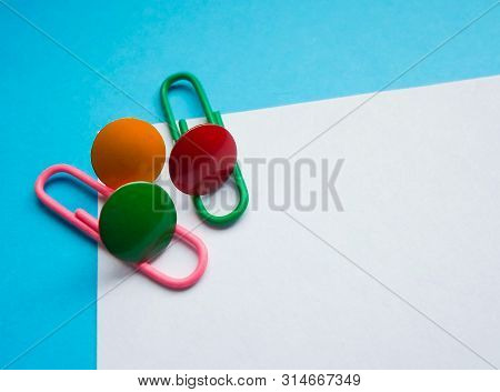 Two Colored Papers With Blue And White Colors, On A White Paper Pink And Green Clip, With Colored Pi