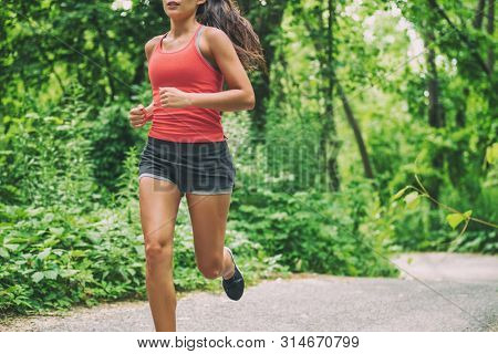 Woman runner on city run marathon race running jogging outdoors in summer active sport lifestyle. Healthy living.