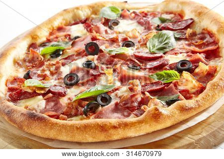 Meat Mix Pizza with Parma Ham, Sausages, Shish Kebab, Bacon, Olives, Tomato Sauce, Mozzarella Cheese Isolated on White Background. Traditional Italian Whole Flatbread on Wood Close Up