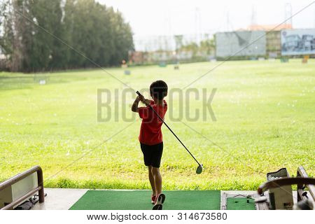 Young Asian Boy Is Practicing His Golf Swing At The Golf Driving Range.