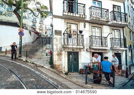Lisbon, Portugal: People Meeting And Drinking Beer And Wine Outside The Bar On Cobbled Street Of Old