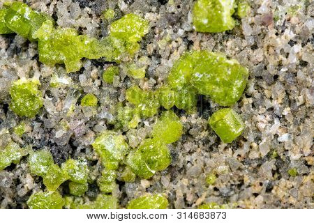 Closeup of a peridot or olivin mineral stone pattern background, details and macro of mineralogy poster