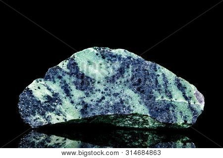 Raw Blue Zoisite Or Saualpite Mineral Stone In Front Of Black Background, Mineralogy And Esotericism