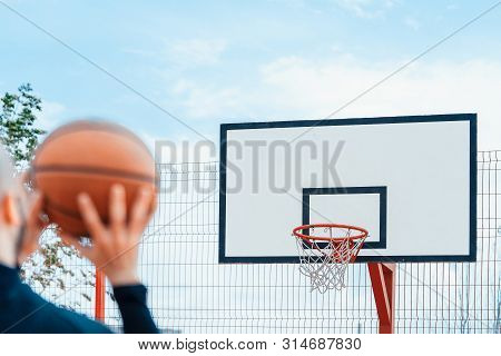 Attractive Man Playing Basketball And Dunking Basketball In Hoop On Basketball Court.